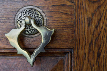 Closeup of antique copper ornate door knocker over an aged wooden door, Fatih Mosque, Istanbul, Turkey