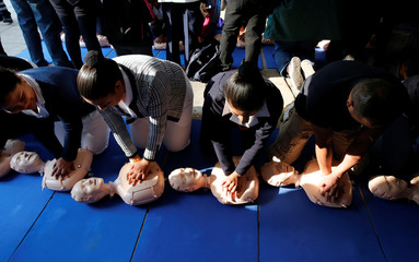 Participants practice cardiopulmonary resuscitation (CPR) during a drill organized by Mexican members of the Red Cross at the Revolution Monument in Mexico City