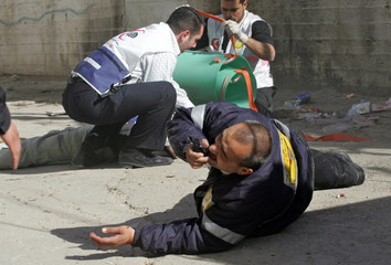 A wounded Palestinian paramedic speaks on the radio next to his wounded colleague during clashes at ..
