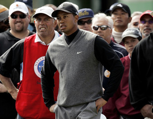 Tiger Woods looks over his shot from trees during Nissan Open golf tournament in Los Angeles
