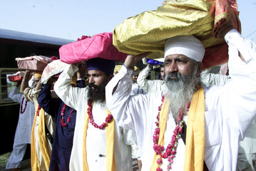 SIKH PILGRIMS CARRY THEIR RELIGIOUS BOOKS ON ARRIVAL AT WAGAH BORDER NEAR LAHORE.