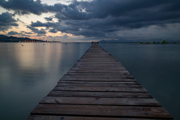 Sunset on a sandy beach and a wooden pier, Panorama
