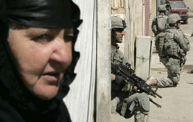 A woman looks out of her house as U.S. soldiers from Delta company 2/325, 82nd Airborne take up positions while on patrol in Baghdad's Sadr City
