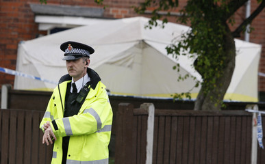 A police officer stands guard near to the house in Manchester, northern England, where three bodies were discovered