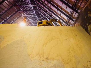 Backhoe handling raw sugar bulk store in bulk warehouse.