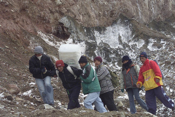 A COMPETITOR IS HELPED TO CARRY A BLOCK OF GLACIAL ICE FROM CAYAMBE'SVOLCANO SLOPES.