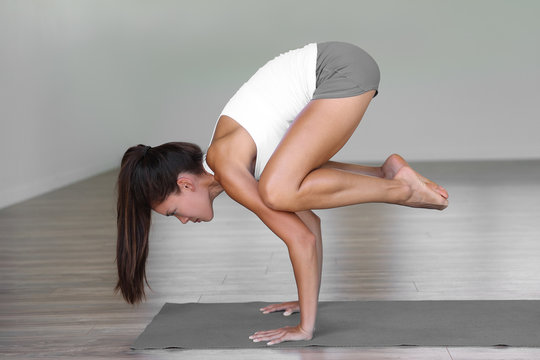 Yoga studio woman doing crow pose in fitness gym class. Girl training arms balance on exercise mat.