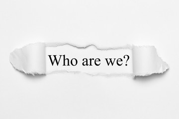 Who are we? on white torn paper