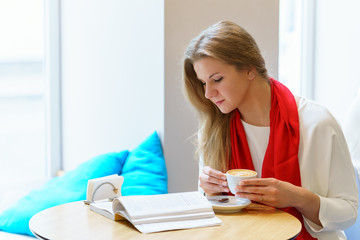 Young attractive europeang woman with red scarf is reading some book close to window and holding cup of cappuccino coffee in her hands