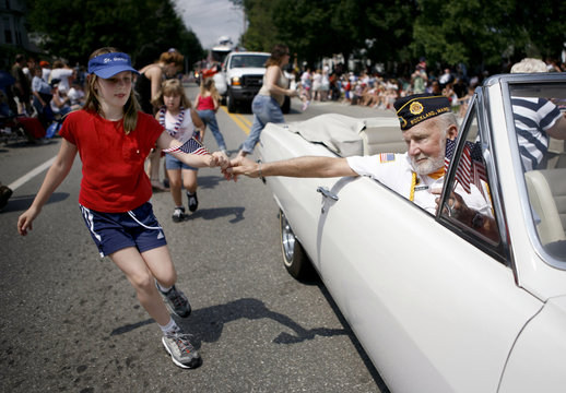 A girl receives American flag from member of American Legion during Independence Day parade in Thomaston