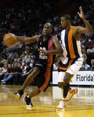 Miami Heat guard Payton drives past guard Taylor of the Washington Wizards during NBA game in Miami