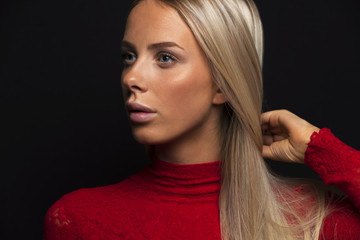 Dark portrait of a beautiful blonde woman in red dress with black bakground