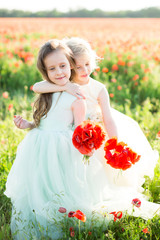 little girl model, childhood, fashion, wedding, summer concept - two young girls bridesmaids summer cuddling on flowered field, in the hands of little models are bouquets of flowers poppy