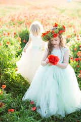 little girl model, childhood, fashion, summer concept - little girlfriend models in white and blue dresses play in a field of blooming poppies, picking flowers and making wreaths on the head