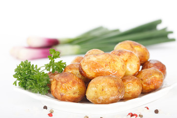 Young roasted potatoes with parsley and spring onions on white background