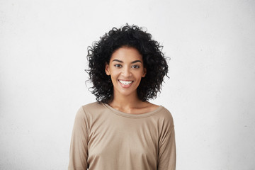 Waist up portrait of casually dressed young mixed race female with curly hair smiling cheerfully during audition for role in TV series, feeling excited and a big nervous, trying to impress director