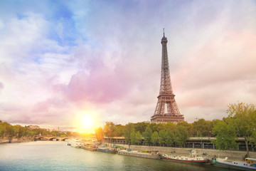 Eiffel tower sunset with clouds. Romantic sunset background. Old Monument with boats on Seine river in Paris, France.