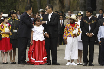 Venezuela's President Chavez and Ecuador's President Correa talk as Bolivia's President Morales looks on during a military ceremony in Quito