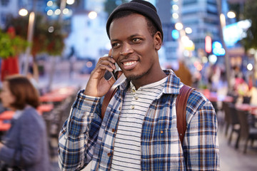 People, urban lifestyle, modern technology and communication concept. Outdoor portrait of handsome trendy looking young black man enjoying night walk around city, talking on mobile phone to his friend