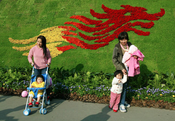 MOTHERS AND CHILDREN STAND IN FRONT OF DRAGON ICON AT FLOWER SHOW INHONG KONG.