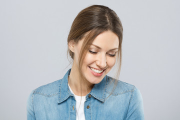 Photo of good-looking woman dressed casually isolated on gray background with eyes looking down in sign of modesty with light shy natural smile indicating pleasure, happiness and indecision.
