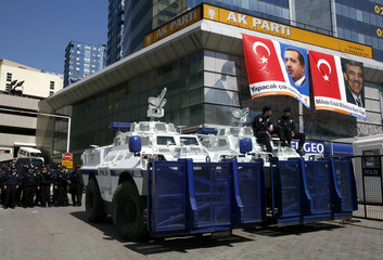 Turkish riot police sit on armoured personnel carriers in front of the city headquarters of ruling AK Party in Istanbul