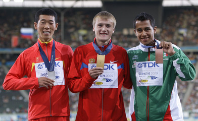 Winners of the men's 20 kilometre walk display their medals during the world athletics championships in Berlin