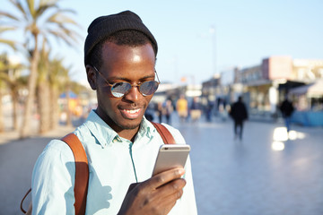 Always in touch. Outdoor shot of smiling cheerful young black European traveler using 3G internet connection on smart phone, messaging his parents that he is doing okay during summer trip abroad