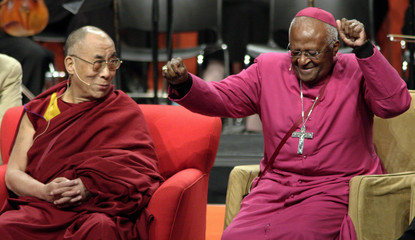 The Dalai Lama watches Archbishop Desmond Tutu dances in his chair as they both take part in a dialogue on youth and spiritual connection  in Seattle