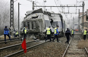 Police and rescue services inspect the front of a French high speed train after a collision with a lorry in La Vavrette