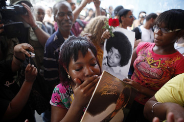 A woman holds a copy of the album 'Thriller', as fans commemorate pop icon Michael Jackson at the Apollo Theater in New York