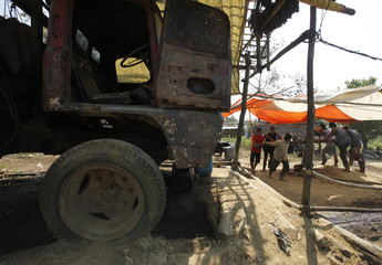 Workers drag an oil bucket near a broken old truck at a traditional oil well at Wonocolo district in Bojonegoro