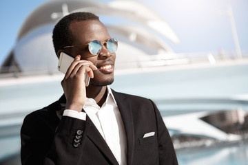 Cheerful young dark-skinned employee in formal wear and round shades talking on smart phone to his wife, sharing great news about promotion at work, having happy look, office building in background