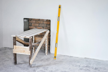Construction grunge ladder, and the building yellow level : white wall and gray floor. Apartment decoration concept.