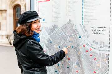 Detail of young woman tourist hand pointing at street city map