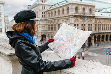 Young brunette eastern or asian woman using city map in Vienna center street