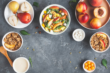Breakfast with muesli, peach salad, fresh fruit, yogurt on dark background. Healthy food concept. Flat lay, top view