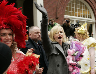 South African actress Theron waves to onlookers after the Hasty Pudding 2008 Woman of the Year parade in Cambridge