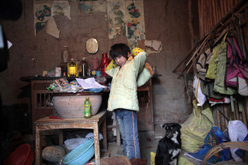 HIV infected girl, Chen Xueyan, 9, adjusts her clothes in her home in Fuyang