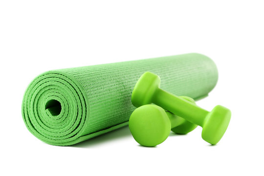 Green dumbbells with fitness mat isolated on white background