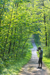 Young man taking photos in a forest