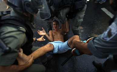 Israeli policemen detain a Jewish rioter after clashes in Acre