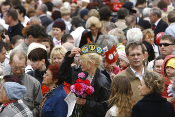 A woman adjusts Soviet army soft cap during World War Two victory celebrations in Riga