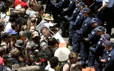 Police form a barricade in front of protesters outside the venue for the G20 summit in Melbourne
