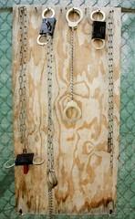 Leg irons and hand cuffs hang on a board at Camp Delta at Guantanamo Naval Base.