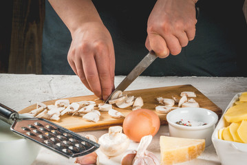 Person is cooking of a traditional French dish - potato gratin: potatoes, milk, cream, eggs, cheese, mushrooms, spices. Casserole. Vegetarian food. Female hands.