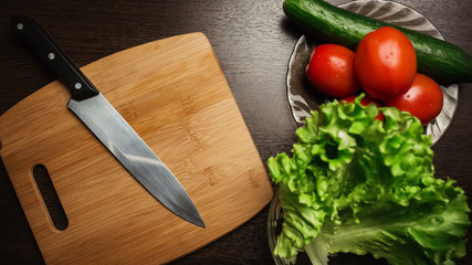 tomato and cut tomato, cucumber and a kitchen knife on a cutting board