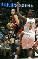 Toronto Raptors forward Anthony Parker looks to pass around Atlanta Hawks forward Josh Smith in the first half of their NBA basketball game in Atlanta.