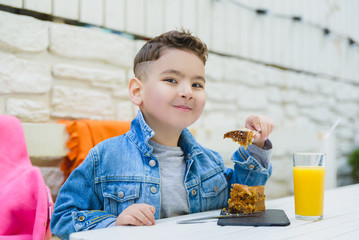 Boy drinking juice and eating pie for healthy breakfast in resort cafe outdoor