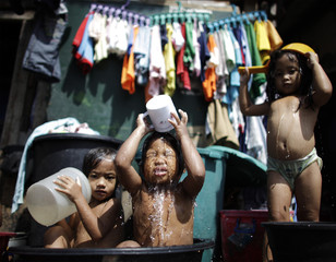 Children take a bath to cool off from the summer heat at a slum area in Tondo